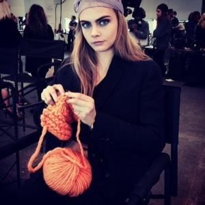 Cara Delevingne lavora a maglia nel backstage di una sfilata